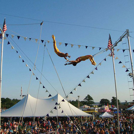 Two trapeze artist fly through the air. The Allen County Fair will feature the High Flying Pages Aerial and Animal Thrill Show in 2017.